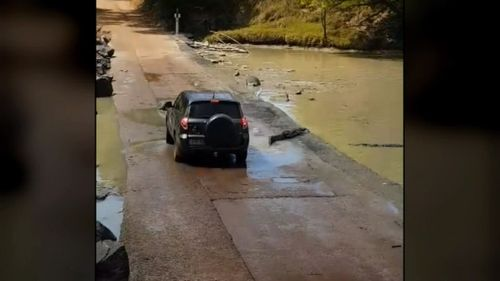 Video shows the moment the 4WD was attempting to drive through Cahills Crossing in Arnhem Land when it was forced to stop due to a group of slow-moving crocodiles in its path.