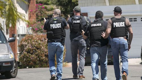 Heavily armed San Diego police officers approach a house thought to be the home of 19 year-old John T Earnest.