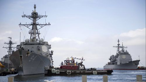 Some naval ships will wait out the storm at sea.