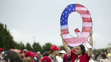 David Reinert holding a Q sign waits in line with others to enter a campaign rally with President Donald Trump and U.S. Senate candidate Rep. Lou Barletta, R-Pa., Thursday, Aug. 2, 2018.
