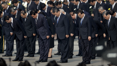 Chinese President Xi Jinping, center, and other officials bow during a ceremony to mark Martyr's Day at Tiananmen Square in Beijing, Monday, Sept. 30, 2019.