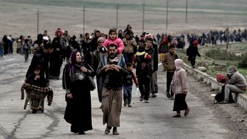 Iraqi families walk down a road as they flee Islamic State in Mosul. (AFP)