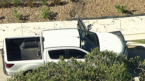 Vision from the crime scene shows a trail of blood on a footpath next to a while dual-cab ute with the door still open.