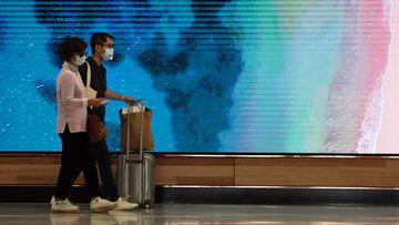 Travellers walk around Sydney International Airport wearing masks