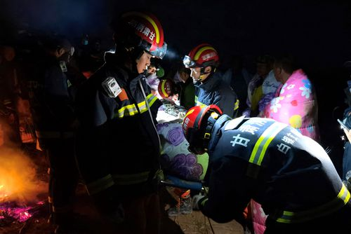 Rescuers assist people who were competing in a 100-kilometre mountain race when extreme weather hit the area, leaving at least 21 dead.