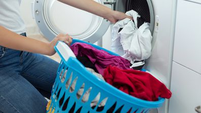 Woman with wet washing doing laundry