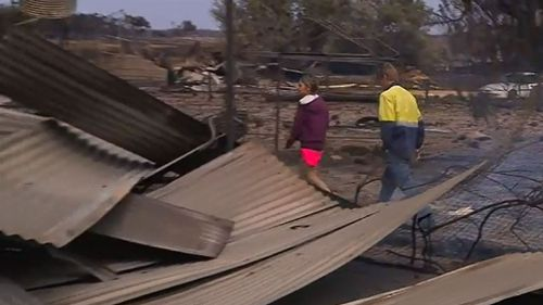 Mr and Mrs Moss inspect their fire-damaged property. (9NEWS)