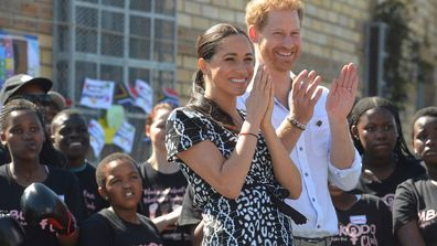 Meghan, left, and Prince Harry, right, greet children and youths on a visit to the Nyanga Methodist Church in Cape Town, South Africa, Monday, Sept, 23,2019.