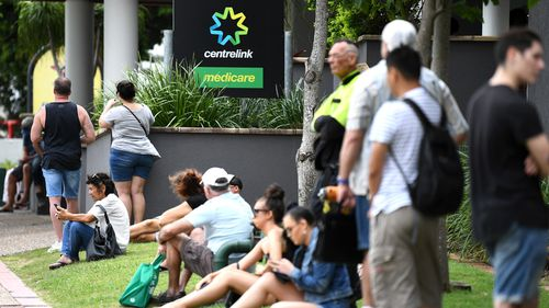 People are seen in long queues outside the Centrelink office in Southport on the Gold Coast. Centrelink offices around Australia have been inundated with people attempting to register for the Jobseeker allowance in the wake of business closures due to the COVID-19 pandemic.