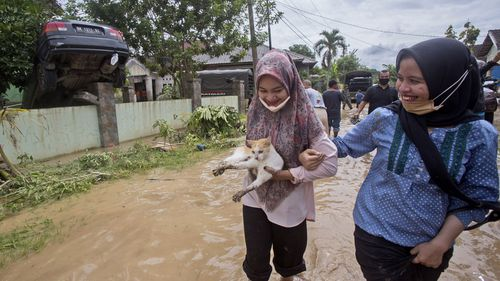 Indonesian women carries a stray cat which was rescued, at an area affected by a flood in Medan, North Sumatra, Indonesia, Friday, Dec. 4, 2020