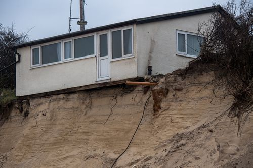 A house on Hemsby beach that has been evacuated after high winds and waves eroded the dunes on which it sits on March 18, 2018 in Norfolk, England. Ten sea front properties have been evacuated after severe weather rapidly eroded the cliff edges in the village of Hemsby. (Photo by Chris J Ratcliffe/Getty Images)