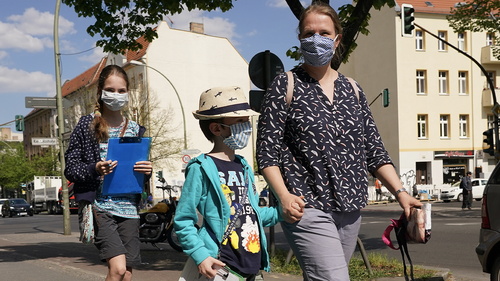 Juliane and her son Paul, 7, and daughter Sarah, 12, wear protective face masks while walking in Baumschulenweg district and working on a school project to map the types of businesses in the street during the coronavirus crisis on April 27, 2020 in Berlin, Germany.