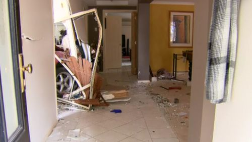 One image captured the car's front wheel wedged in the wall leading to the hallway. (9NEWS)