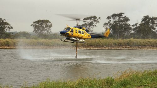 In this photo provided by Costi Farms a helicopter refills it's tank to help fight a wildfire as it moves through Deepwater National Park