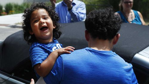 Ever Reyes Mejia, of Honduras, carries his son to a vehicle after being reunited and released by United States Immigration and Customs Enforcement in Grand Rapids. (AAP)