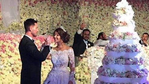 A tiny glimpse of the lavish wedding ceremony, with the wall of flowers and 10-tier wedding cake in sight. (Facebook)