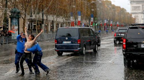 A topless woman is tackled by police as she runs towards President Donald Trump's motorcade in Paris.