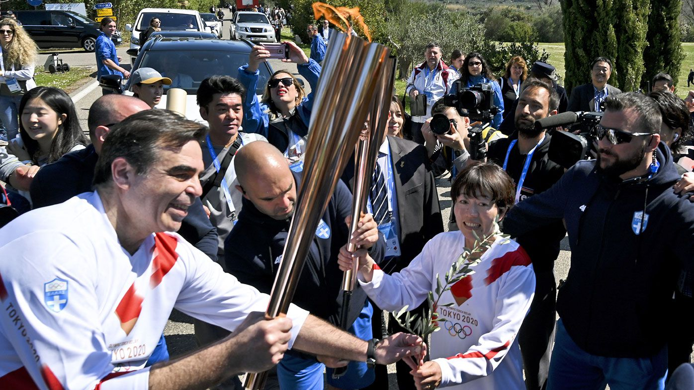 Second torchbearer, Japanese former marathon runner Noguchi Mizuki, passes the Olympic flame to the third torch bearer, European Commissioner Margaritis Schinas