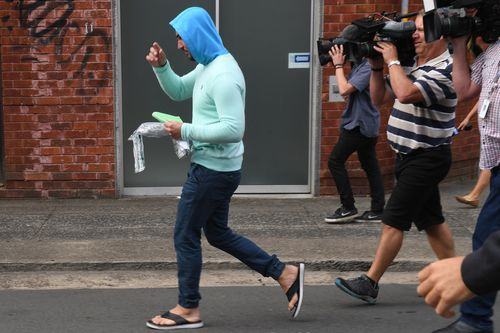 He's pursued by a pack of media as he leafs through his papers. Picture: AAP