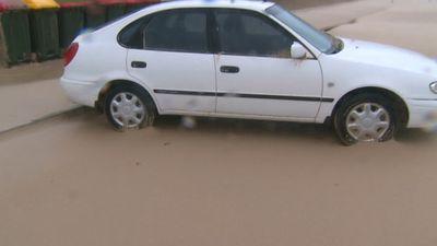 A car stuck in a sandblasted street. (9NEWS)