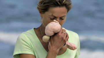 Kate McCann, mother of missing girl Madeleine, takes a walk on the beach on May 13, 2007, in Praia da Luz, Portugal. Kate is holding her daughter's toy.