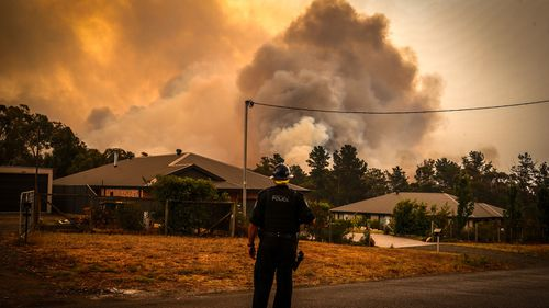 A policeman watches bushfires as they approach homes located on the outskirts of the town of Bargo on December 21, 2019 in Sydney, Australia