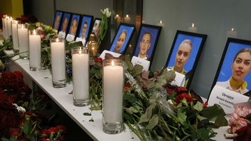 Flowers and candles are placed in front of portraits of the flight crew members of the Ukrainian 737-800 plane.