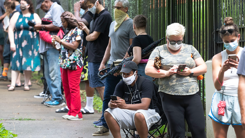 In this June 9, 2020, file photo, Steven Posey checks his phone as he waits in line to vote at Central Park in Atlanta.
