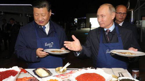 Russian President Vladimir Putin and China's President Xi Jinping make pancakes as they visit the Far East Street exhibition at the Eastern Economic Forum in Vladivostok, Russia.
