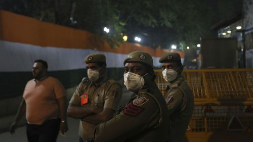 policemen wear pollution masks and guard outside a cricket stadium in New Delhi.