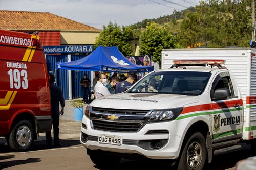 Police vehicles and relatives of children stand outside the Aquarela creche in Saudades.