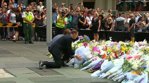 Prime Minister Tony Abbott and his wife Maggie Abbott arrive to pay their respects at the floral memorial in Martin Place. (9News)