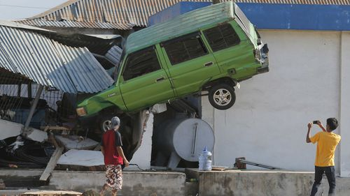 The force of the tsunami in Indonesia slammed cars into buildings.