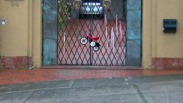 A child's tricycle was left tied to the gate of the residence Cardinal George Pell spent the night at. A day earler the High Court overturned all convictions againbst Pell.