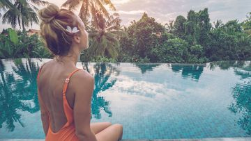 Young woman sitting by a swimming pool in Bali.