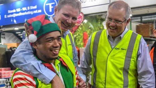 Federal Treasurer Scott Morrison (second right) and member for Reid Craig Laundy (second left) visit the Sydney Markets in Homebush