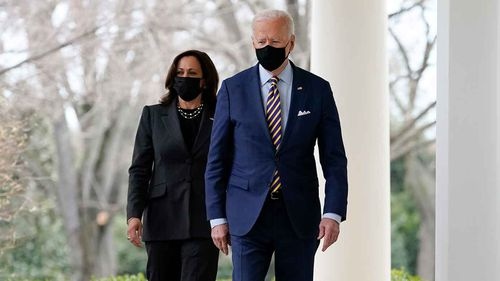 President Joe Biden and Vice President Kamala Harris walk along the White House colonnade as they arrive to speak in the Rose Garden in Washington.