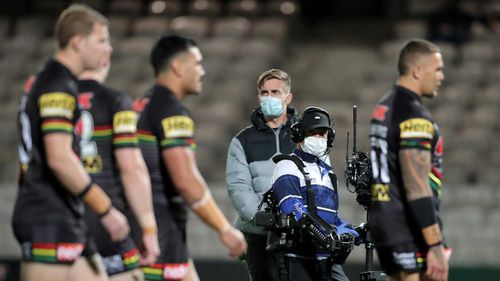 Media broadcast members are seen wearing masks and gloves before the round seven NRL match between the Penrith Panthers and the South Sydney Rabbitohs.