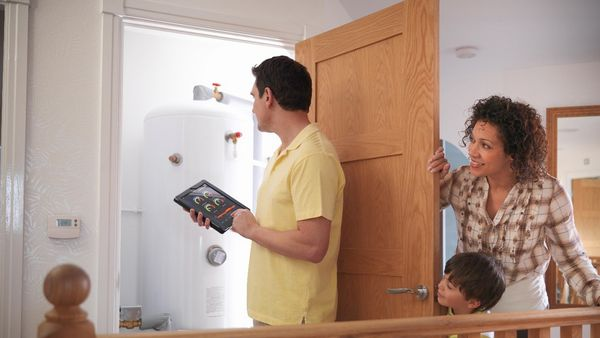 Family inspecting hot water cylinder