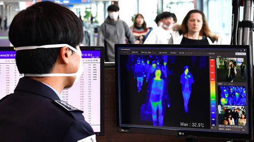 A thermal camera monitor shows the body temperature of passengers arriving from overseas at Incheon International Airport in Incheon, South Korea