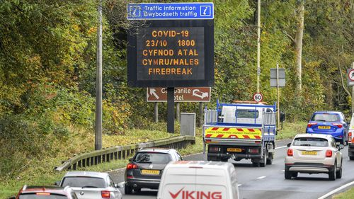 """A matrix sign on the A48 motorway heading towards Cardiff informing motorists to Wales entering a """"firebreak"""" lockdown, Friday, Oct. 23, 2020"""