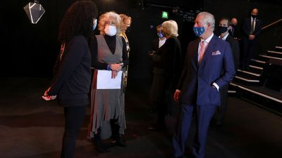 Prince Charles, Prince of Wales (R) wears a face mask as he speaks to a performer and Chair of Soho Theatre Dame Heather Rabbatts (second left) during his visit to Soho Theatre with Camilla, Duchess of Cornwall to celebrate London's night economy