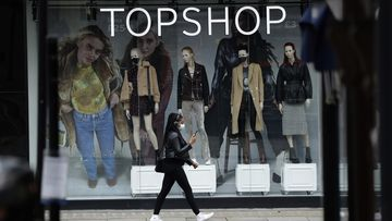 A woman wearing a face mask walks past mannequins wearing face masks in the window of a temporarily closed branch of the Topshop women's clothing chain during England's second coronavirus lockdown, in London.