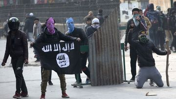 A Kashmiri protester shows Islamic state flag as others clash with Indian policemen during a protest in Srinagar, Indian controlled Kashmir on December 7.