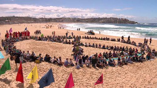 Extinction Rebellion activists form logo on sand at Bondi Beach