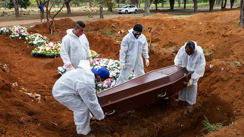 Cemetery workers in protective suits bury Elisa Moreira de Araujo, 79, a victim of coronavirus (COVID-19) at the Vila Formosa cemetery on July 16, 2020 in Sao Paulo, Brazil.