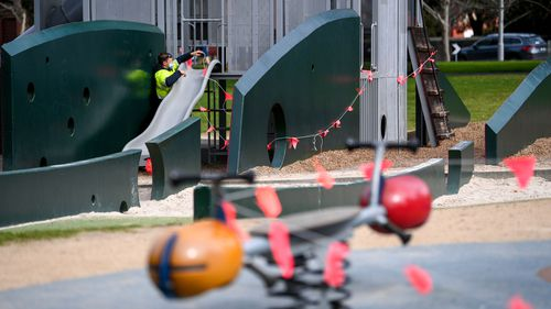 Playgrounds at the Carlton Gardens pictured being closed by local council staff due to COVID restrictions.