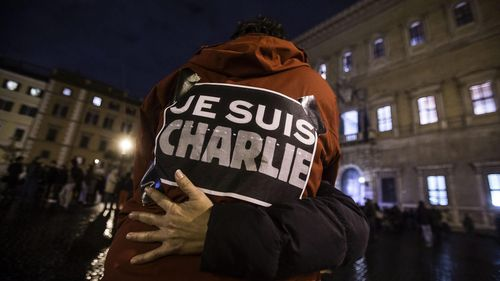 People embrace outside the French embassy in Rome, Italy during a tribute to the Charlie Hebdo victims. (AAP)