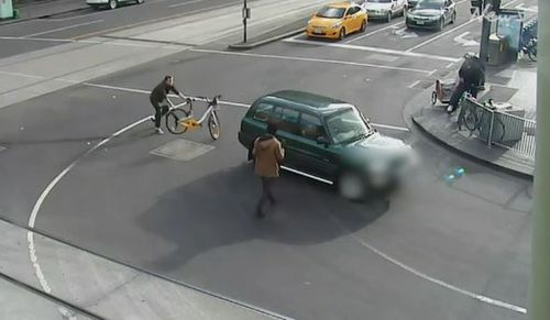 A man attempting to stop the driver throws his hire bicycle behind the vehicle. (Herald Sun)