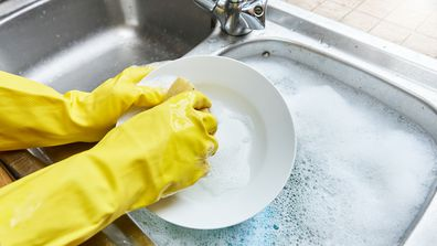 Wearing rubber gloves washing the dishes